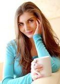 Young beautiful woman drinking tea at home — Stock Photo