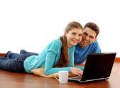 Souriante jeune couple avec ordinateur portable à la maison — Photo
