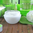 Stock Photo: Creams for body care in transparent and green containers