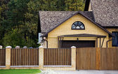 Brick house and fence in an environment — Stock Photo