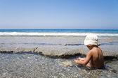 Little boy plays on an ocean coast — Stock Photo