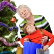 Grandmother and little girl with gift bags near Christmas tree. — Stok fotoğraf