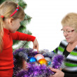 Grandmother with the grand daughter decorate a Christmas tree — Stock Photo