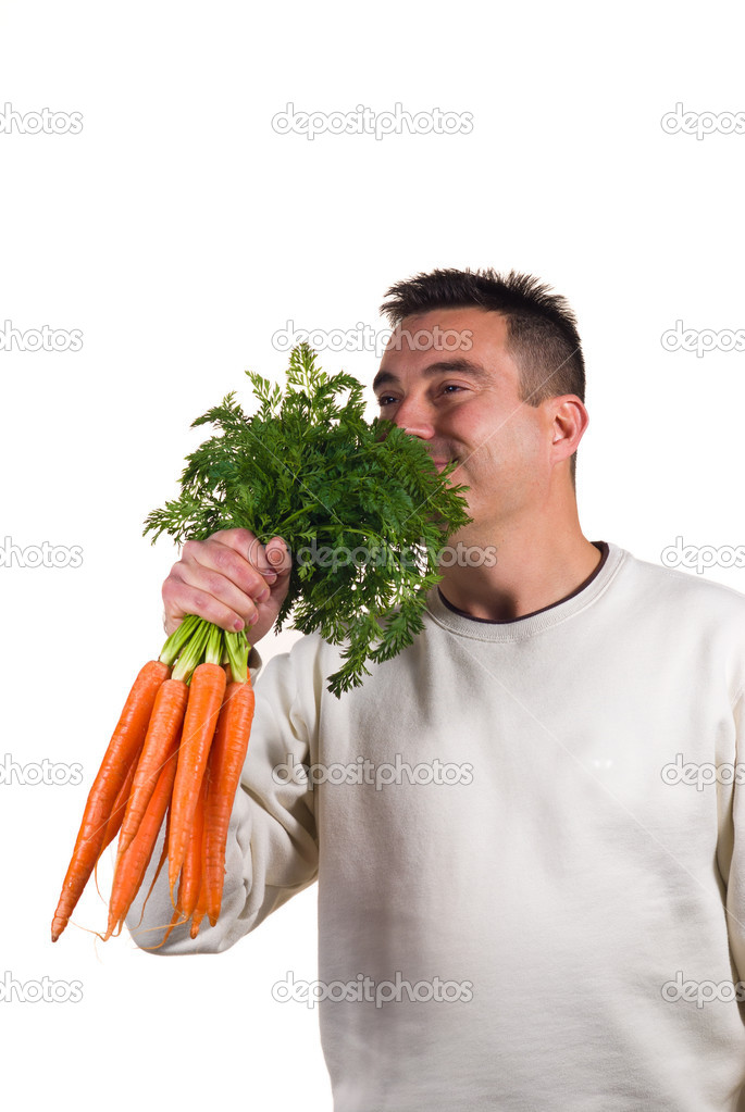 Guy happily holding a bunch of carrots, dieting concept  Stock Photo #9234529