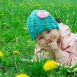 Baby girl lying among field of dandelions — Stockfoto