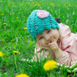 Stock Photo: Baby girl lying among field of dandelions