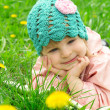 Foto Stock: Baby girl lying among field of dandelions