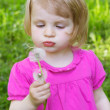 Baby girl blowing dandelion — Stock Photo