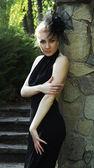 Woman in black dress near stone wall — Stock Photo