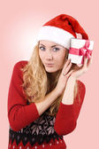 Woman in Santa hat holding present — Stock Photo