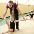 Young gymnast with coach — Stock Photo
