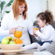 Mother gives daughter juice — Stock Photo #10303346