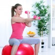 Woman in sportswear, doing fitness exercise with dumbbell - Stock Photo