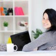 Happy young woman sitting on sofa using laptop — Stock Photo #10304314