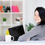 Happy young woman sitting on sofa using laptop — Zdjęcie stockowe #10304314