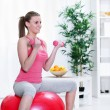 Female sitting on a fitness ball with dumbbells — Stock Photo #10304902