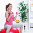 Female sitting on a fitness ball with dumbbells — Stock Photo
