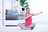Smiling young woman doing stretching exercise. — Stock Photo