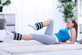 Young girl doing exercising with legs weights — Stock Photo