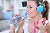 Woman with water bottle and measuring tape — Stock Photo