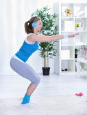 Sportive lady doing squatting at home — Stock Photo