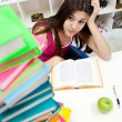Worried student girl looking in books — Stockfoto