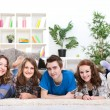 Stock Photo: Teenagers friends lying on floor in row