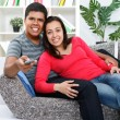 Couple watching TV in their living room — Stockfoto