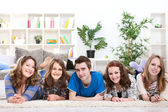 Teenagers friends lying on floor in row — Stock Photo