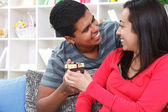 Attractive young male surprises his girlfriend — Stock Photo