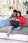 Young happy couple in the living room — Stock Photo