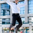 Happy businessman jumps in the air - Stockfoto