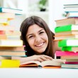 Teenage girl between stack of book — Stock Photo