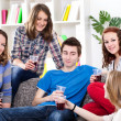 Group of teenagers sitting on sofa at home — Stock Photo