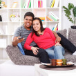Stock Photo: Smiling young couple watching TV