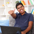 Smiling boy with laptop showing thumbs up — Stock Photo #10635091