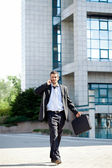 Businessman talking on phone while walking — Stock Photo