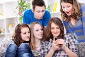 Surprised friends looking in smart phone — Stock Photo
