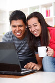 Happy young couple looking at a laptop — Stock Photo