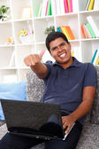 Smiling boy with laptop showing thumbs up — Stock Photo