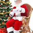 Santa in rocking chair reading letter — Stock Photo #8123277