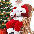 Santa in rocking chair reading letter - Stock Photo