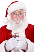 Santa Claus offering a gift — Stockfoto