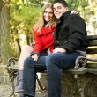 Happy couple sitting on bench — Stock Photo