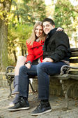 Happy couple sitting on bench — Stock Photo