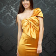 Young model in golden dress — Stock Photo