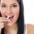 Постер, плакат: Beautiful girl taking white chewing gum smiling