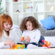 Mother and girl playing on living room floor — Stock Photo #9772492