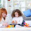 Mother and girl playing on living room floor — Stock Photo