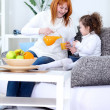 Mother and daughter drinking orange juice — Stock Photo #9772655